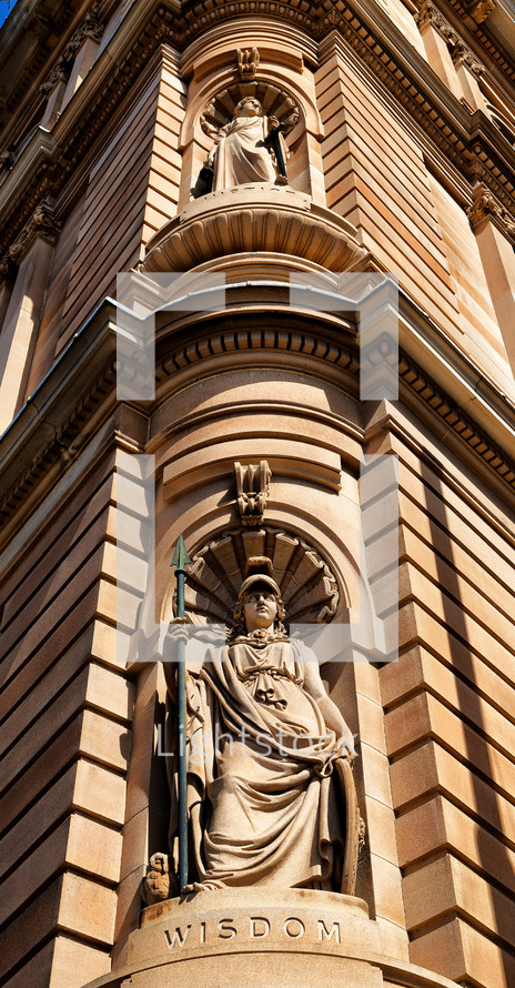 statue of wisdom carved into the corner of a building