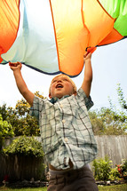 toddler boy holding a parachute