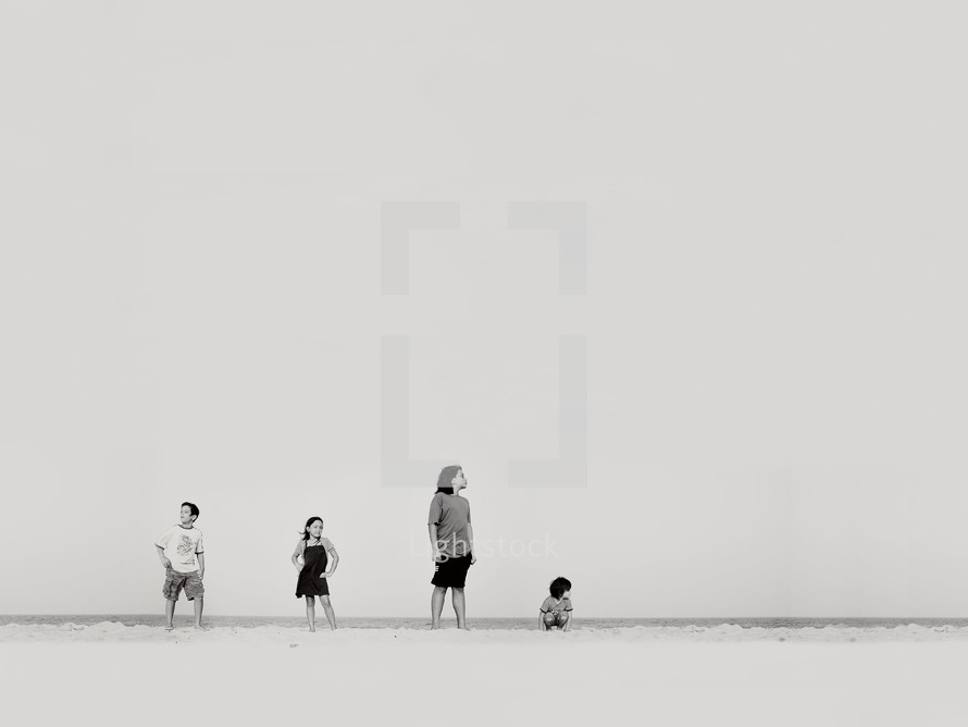 children standing and posing on a beach