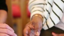elderly women holding hands in prayer