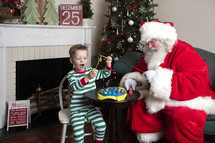 Santa and a little boy playing with toys
