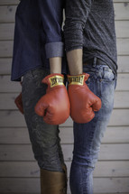 fighting couple wearing boxing gloves standing back to back