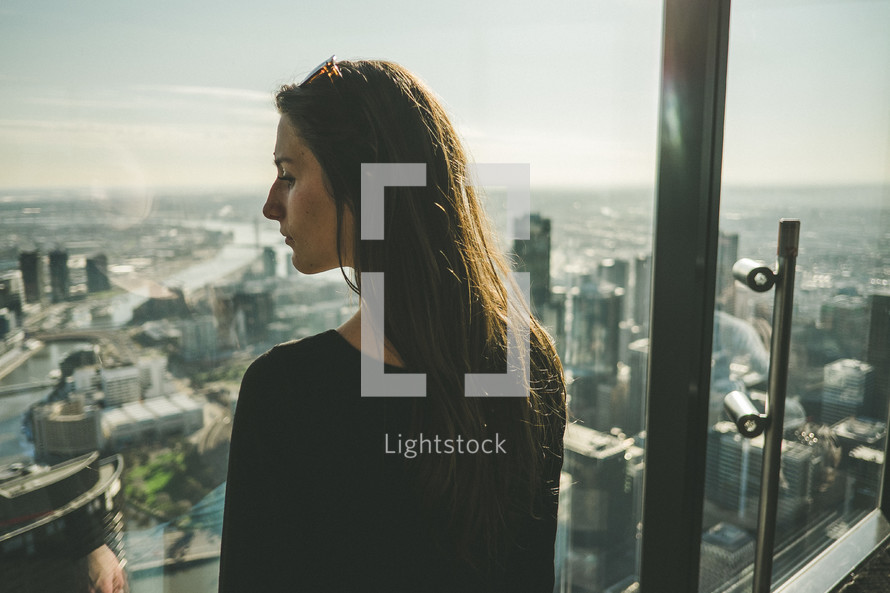 A woman looking from a window of a high rise building across a city.