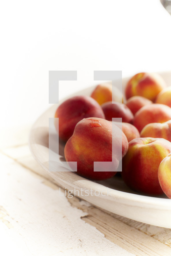 A cluster of peaches set in a bowl.