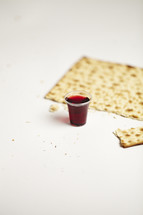 A communion cup and broken cracker isolated on white
