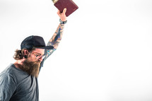 man holding a Bible up in worship to God