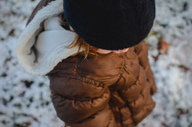 a little girl in a coat standing in snow