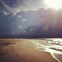 tide washing onto a beach under a cloudy sky
