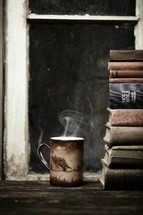 Steaming hot cup of coffee sitting on wood table next to a stack of books