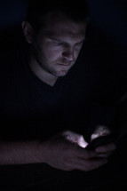 a man texting in darkness