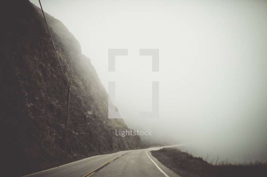 mountain road under thick fog
