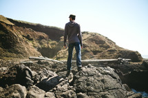 man standing on rocks on a shore