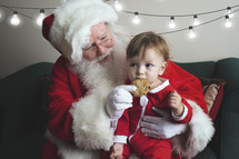 a toddler eating cookies on Santa's lap