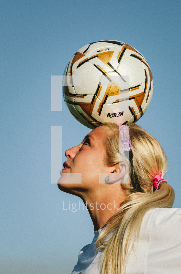 soccer player balancing a ball on her head