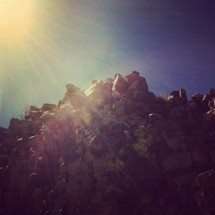 sunburst over a rock covered mountain top