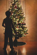 boy child with a stuffed animal standing in front of a Christmas tree