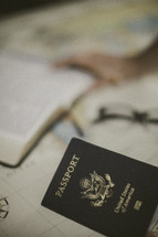 Bible, reading glasses, and passport on a map, missions preparation