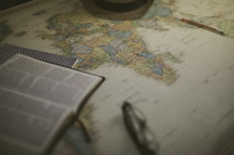 Bible, reading glasses, and hat on a world map, missions preparation