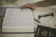 open Bible, passport, and reading glasses on a world map