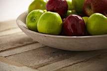A bowl of green and red apples rest on a wooden table.
