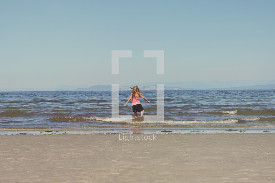 beach and sky with girl in water