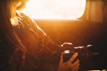 Golden sunlight on a woman with a camera.