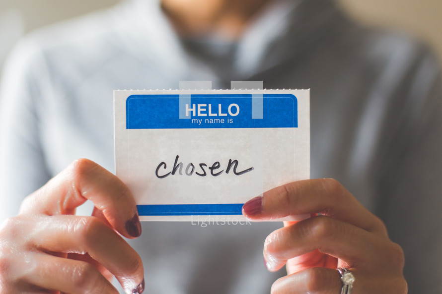 woman holding a name tag with the word chosen