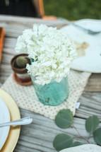 Mason jar of flowers on a picnic table outside.