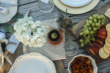 Place settings with fruits, nuts and flowers on a picnic table outside.