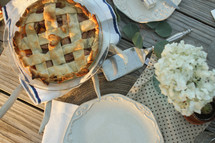 Bouquet of flowers, plates, and an apple pie on a picnic table outside.