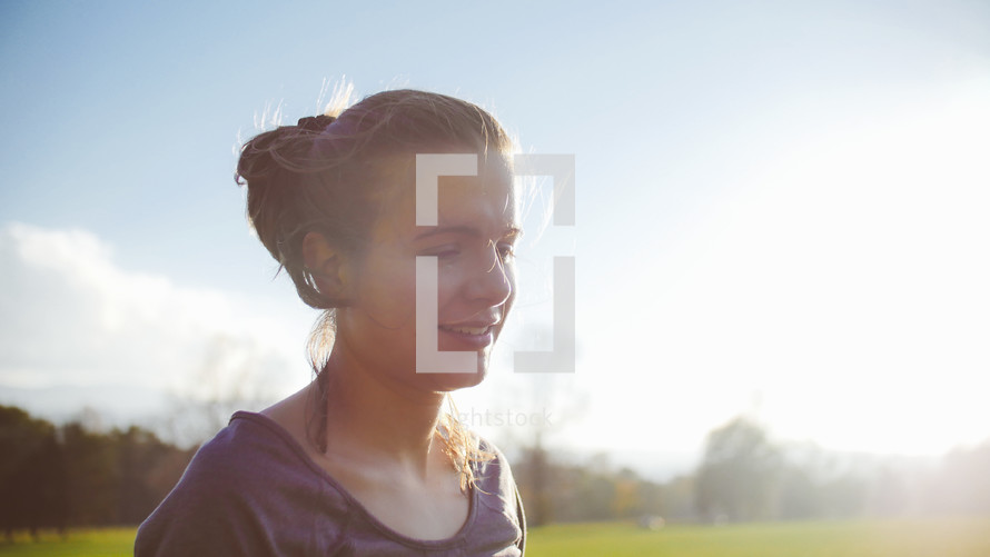 face of a woman standing in a field of cut green grass