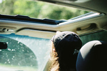 A person wearing a hat and riding in the passenger seat of a car.