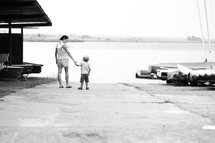 mother walking with toddler son on a boat ramp