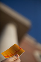 hand holding a Christian tract in front of columns of a college building