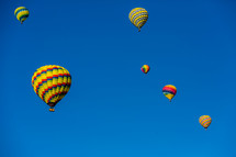 Brightly colored hot air  balloons in a blue sky.