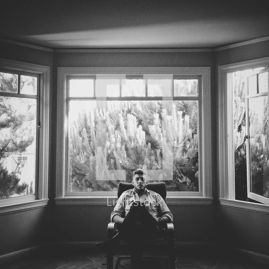man sitting in a chair in front of a window