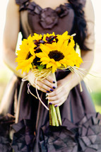 Woman holding sunflower bouquet