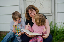 a mother reading a Bible to her children outdoors
