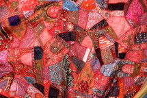 Multicolored crazy quilt made from small pieces of colored cloth with silver thread stitching