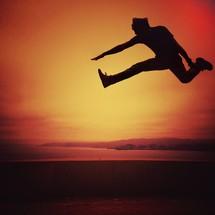 Man jumping in midair at sunset