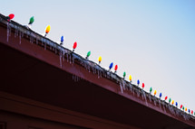Christmas lights and icicles on a gutter