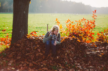 a woman sitting in a pile of fall leaves