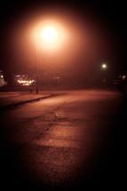 a glowing streetlight on a dark street at night