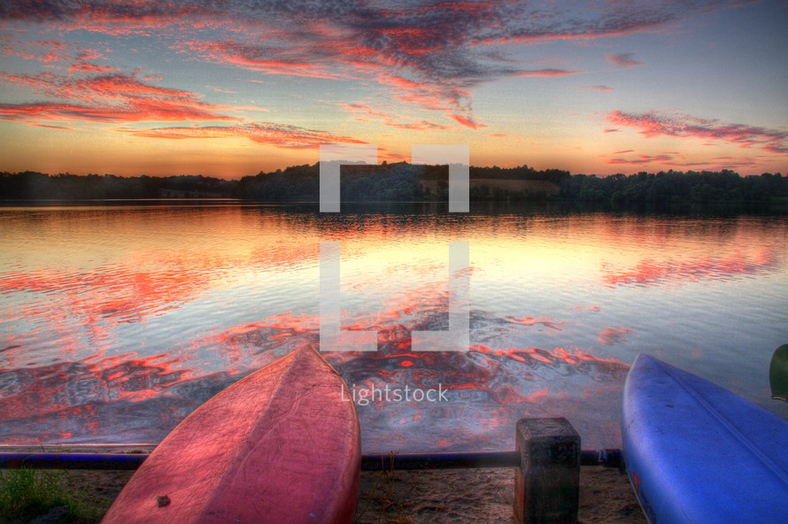 pink and purple clouds reflecting on lake water in front of two flipped over  boats resting on a shore