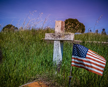 American flag next to a cross grave marker in an old cemetery