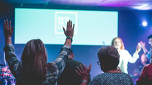 people on stage singing at a worship service and raised hands in the audience