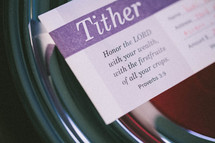Tithing envelope resting inside an offering plate