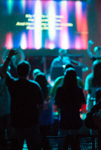 teens with raised hands at a youth worship service