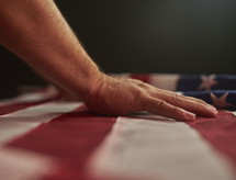 Person with hand on flag - Pray for the Nation