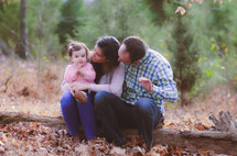 mother, father, and toddler sitting on a fallen tree in fall
